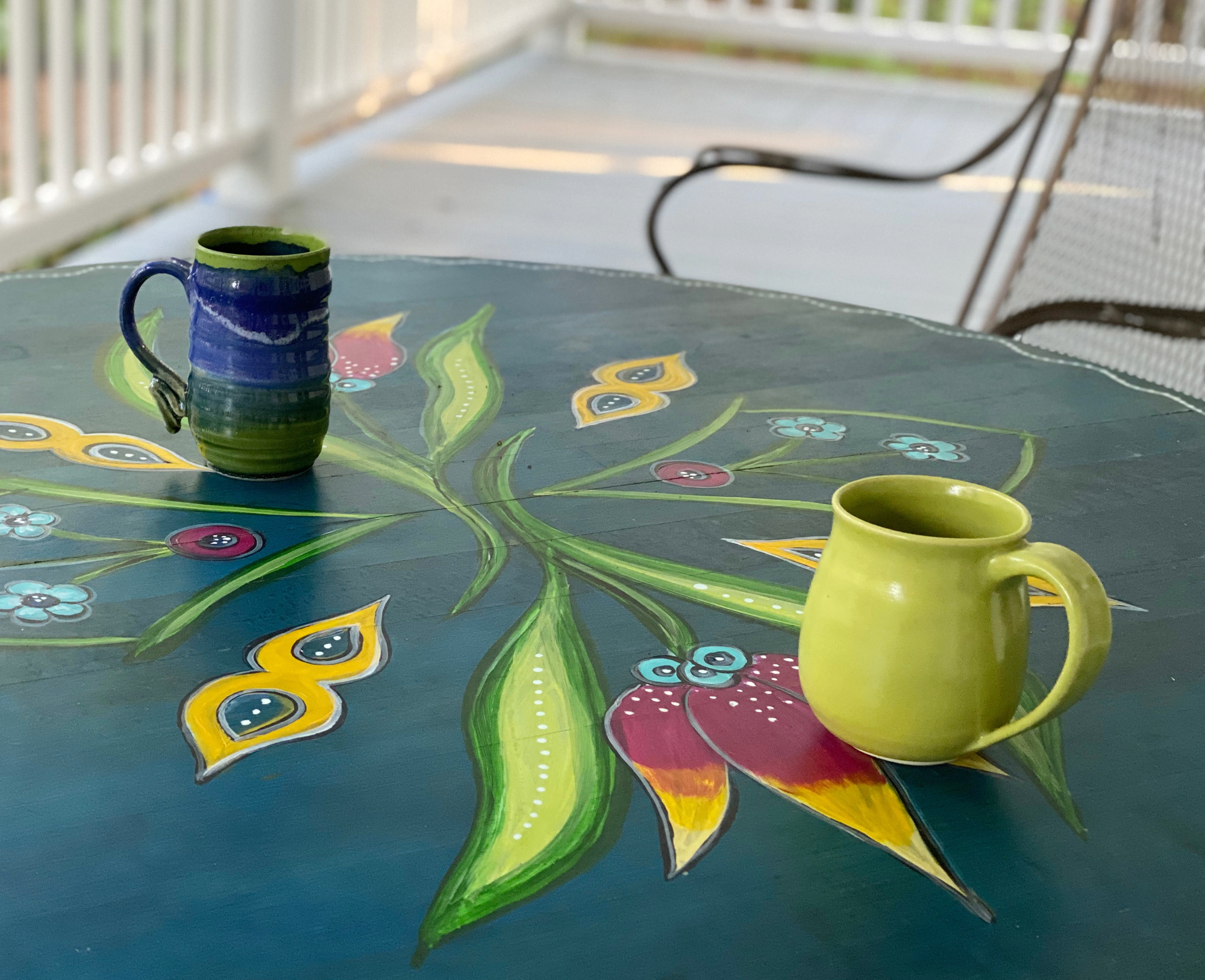 Two coffee mugs on painted table on porch